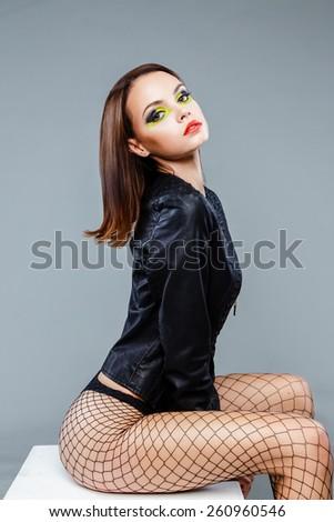 Sexy seductive brunette female fashion model with bright make up posing in studio - stock photo
