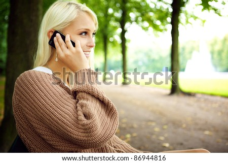 Sexy sensual blonde female model In animated conversation on her mobile phone in the park. - stock photo