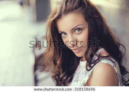 Sexy sensual woman posing with big eyes and full lips at evening sunlight at city park. - stock photo
