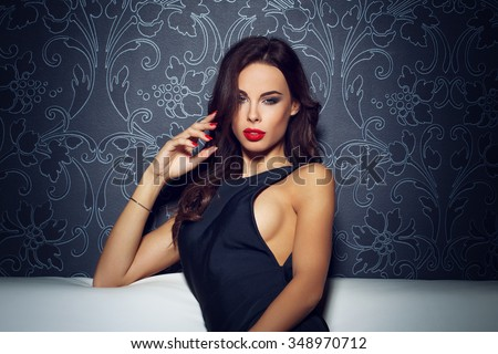 Sexy sensual woman sitting on sofa, red lips, seduction