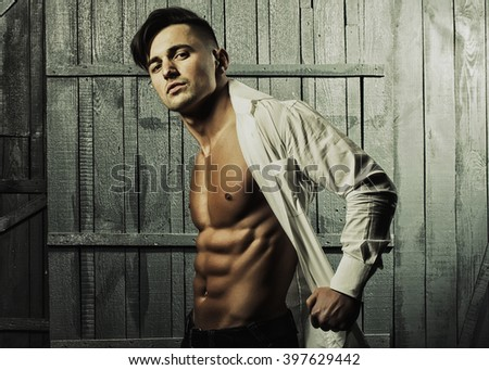 Sexy serious sensual muscular young macho man with bare torso in white shirt standing indoor on wooden background, horizontal picture - stock photo