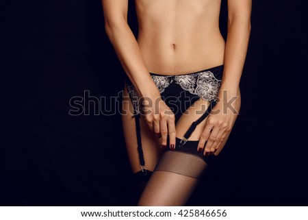 Sexy shapely woman legs in black belt lace lingerie stockings - stock photo