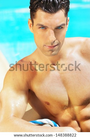 Sexy shirtless handsome male model with sparkling blue eyes against blue swimming pool background - stock photo