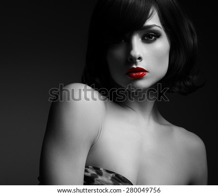 Sexy short hair woman with red lips in darkness. Black and white portrait. Shadow on half face