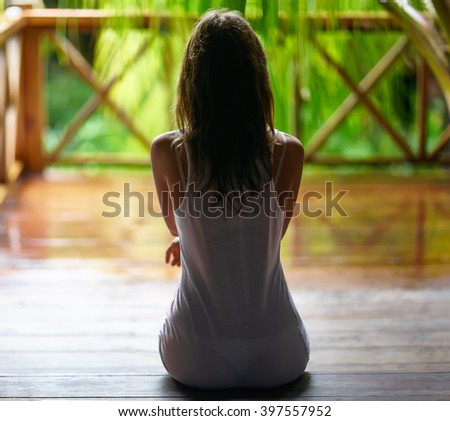 Sexy silhouette of a young woman sitting on the porch during the rain. Back view - stock photo