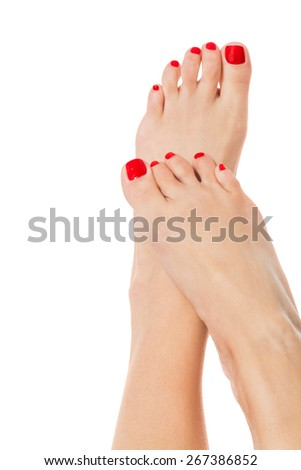 Sexy slender female feet with carefully pedicured fashionable red nails displayed in the crossed position on white with copyspace - stock photo