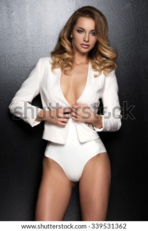Sexy slim blonde woman posing in studio wearing fashionable jacket and pants  - stock photo