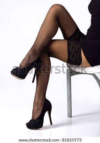 sexy slim long legs in black stockings and shoes on the chair
