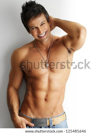 Sexy smiling shirtless male model flirting against white background - stock photo