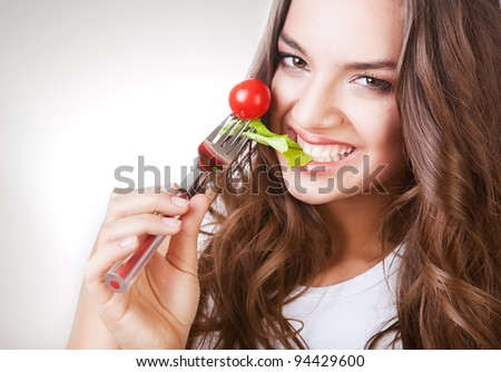 sexy smiling woman biting salad - stock photo