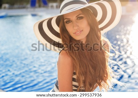 Sexy smiling woman is wearing stripped dress and hat with tanned skin and perfect figure is standing near pool, summer time - stock photo