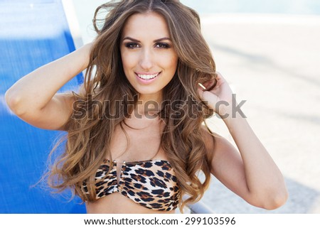 Sexy smiling woman with tanned skin is sitting near swimming pool on sunbed, summer time - stock photo