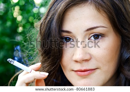 Sexy smoking woman with beautiful face posing outdoors - stock photo