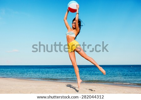 sexy sportive tan woman  with perfect  body playing ball  on the summer beach . Wearing yellow shirts, colorful  top and cool glasses. - stock photo