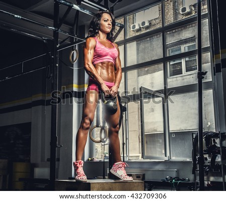 Sexy sporty female in pink sportswear holding barbell in cross fit club. - stock photo