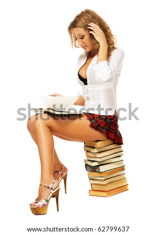 Sexy student girl sitting on a stack of books against white background - stock photo