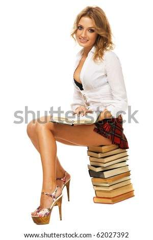 Sexy student girl with a stack of books against white background