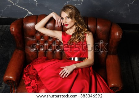 Sexy stylish blonde beautiful woman on the leather sofa - stock photo