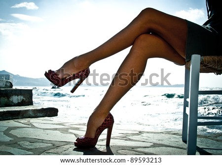 Sexy summer legs in high heels by the sea in Mykonos, Greece. Backlit image. - stock photo
