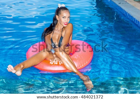 Sexy suntanned lady with long legs and silky hair swims in big pink inflatable circle in swimming pool. She smiles to the camera