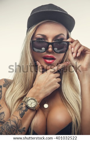 Sexy tattooed female in sunglasses and black cap isolated on a white background. - stock photo
