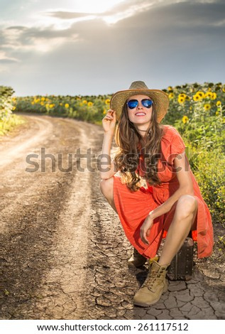 Sexy traveler on rural road during sunset over dramatic sky and summer field - stock photo