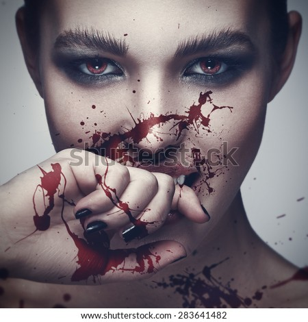 Sexy vampire woman with blood on her face - stock photo