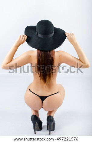 Sexy voluptuous sensual girl wearing thongs, hat and high heels posing in studio isolated on white background.