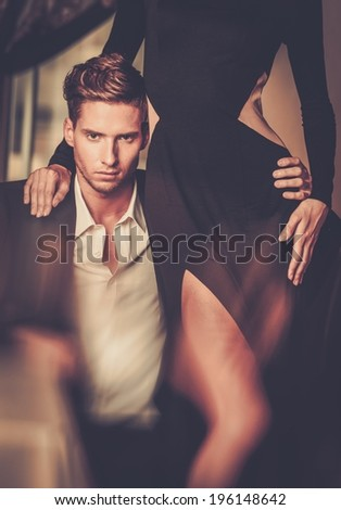 Sexy well-dressed young couple in luxury interior - stock photo