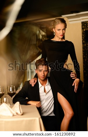 Sexy well-dressed young couple in luxury restaurant interior  - stock photo
