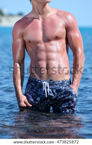Sexy wet muscular torso of a young guy in the ocean in a shorts