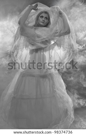 Sexy witch dressed up in white dress covered in smoke - stock photo