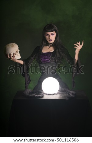 Sexy witch in a corset holding a human skull in her hand, studio shot