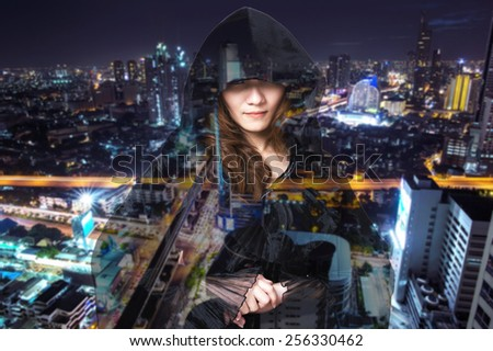 Sexy witch with the city at night - stock photo