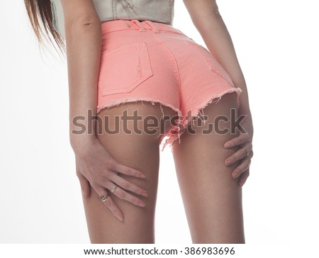 Sexy woman body in jeans shorts. The model is back. Great ass. Studio shot on white background. - stock photo