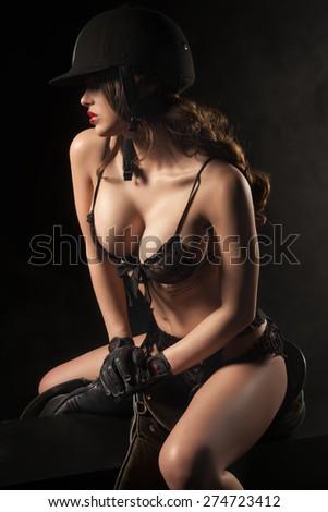 Sexy woman body with saddle and helmet like jockey  - stock photo