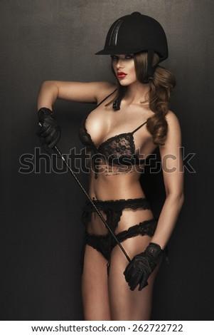 Sexy woman body with whip and helmet like jockey  - stock photo