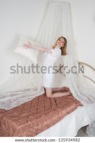 sexy woman doctor on the bed throwing pillows