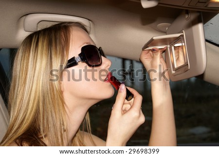 Sexy woman doing makeup in the car