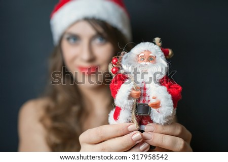 Sexy woman dressed in Santa Claus clothes gives you a toy of Santa. Black background