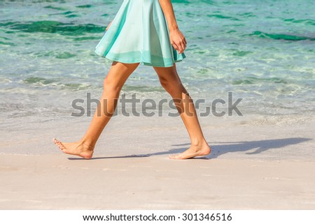 Sexy woman dressed with green skirt walking bare foot on the beach shore. Closeup of her tanned naked shaved legs. Closeup detail of female feet and white sand.