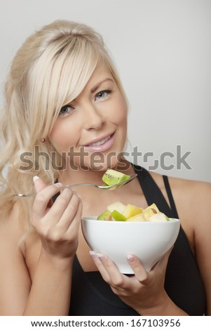 sexy woman eating from a bowl of fresh fruit salad - stock photo