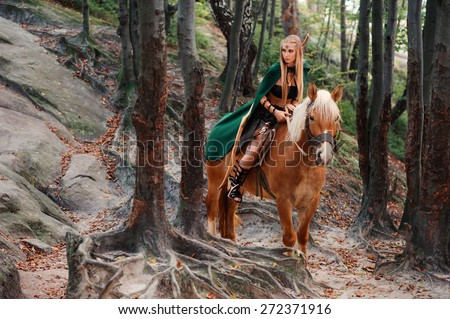 sexy woman elf warrior on horseback in the woods - stock photo