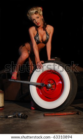 Sexy Woman Fixing a Wheel - stock photo