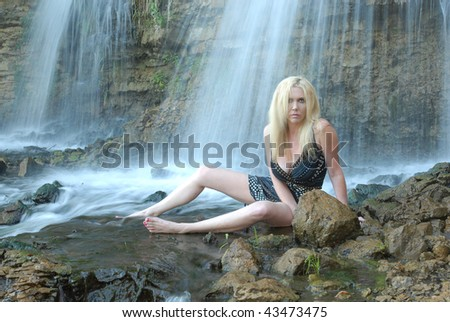 Sexy woman in a black dress sitting in a waterfall.