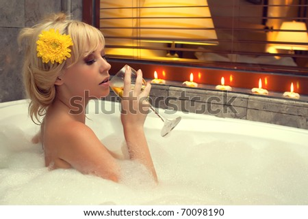 Sexy woman in a jacuzzi with a glass of wine - stock photo