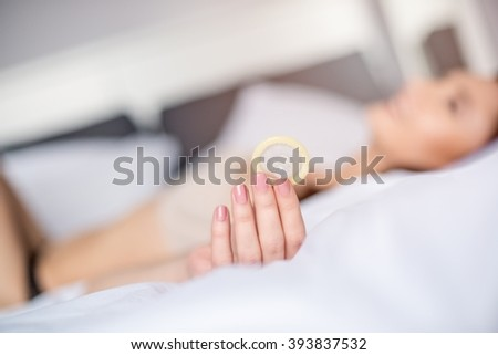Sexy woman in bed is holding a condom for a safe sex. Safe sex concept - stock photo