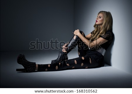 Sexy woman in black clothes in dark room - stock photo