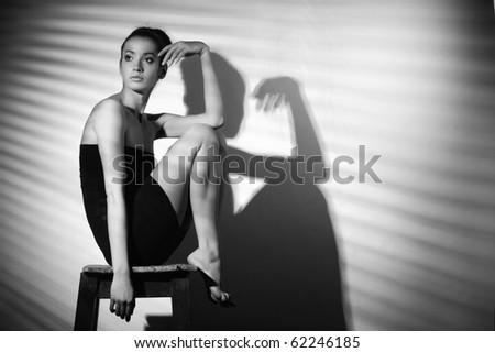 sexy woman in black dress sitting - stock photo