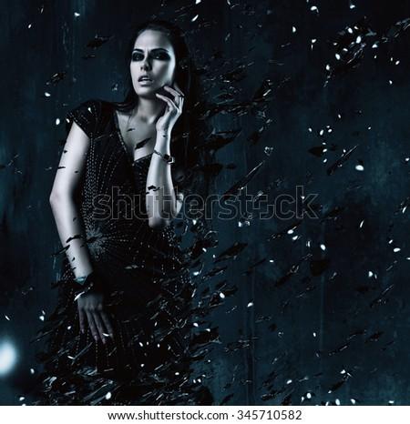 sexy woman in black dress with broken glass around in dark room - stock photo